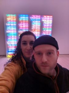 Jess and Tim in front of a neon installation